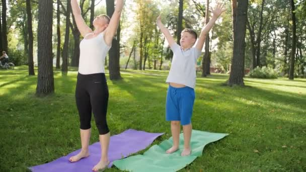 4k záběry dospívajících chlapečka praktikující jóju s matkou středního věku na trávě v parku. Rodina provádí fitness cvičení a roztažení v lese