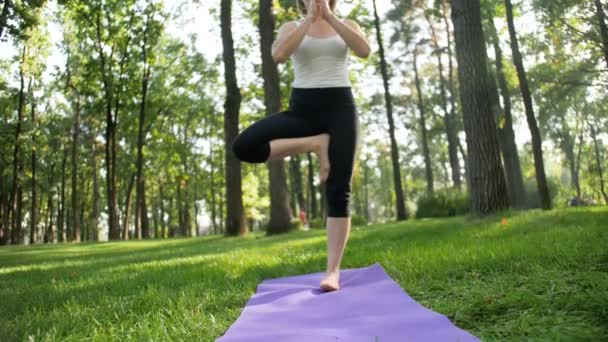 4k footage of happy smiling woman stretching on fitness mat at park. Middle aged lady doing yoga exercises at forest.