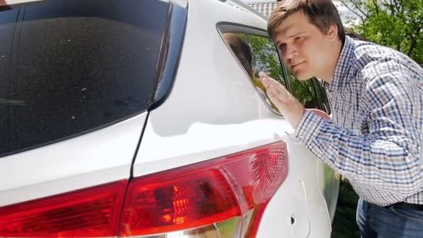 4k video s úsměvem mladého muže, který se dotýká rukou svého nového čistého auta