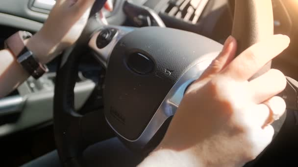 Closeup slow motion footage of female driver holding steering wheel and driving a car at bright sunny day