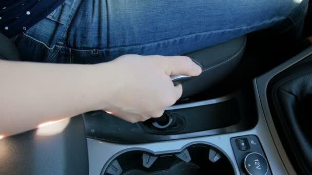 Nahaufnahme in Zeitlupe: Autofahrerin zieht Handbremshebel beim Einparken