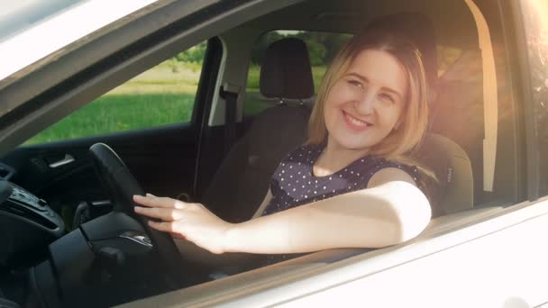 Slow motion video of beautiful smiling woman sitting in car and looking out of the open window