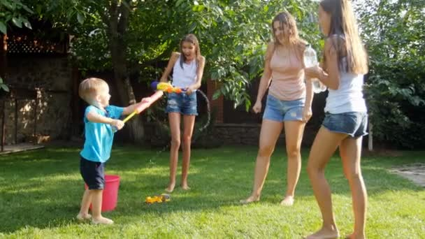 Slow motion video of happy family splashing water on each other at backyard garden