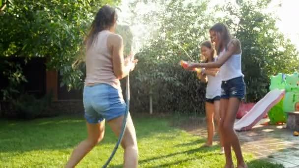 Zeitlupenvideo von glücklichen Kindern und Erwachsenen, die an heißen Sonnentagen Wasser aus Wasserpistolen und Gartenschlauch übereinander spritzen