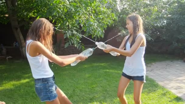 Zeitlupenaufnahmen von zwei Teenager-Mädchen, die Wasser aus Plastikflaschen übereinander spritzen