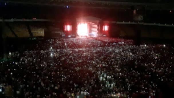 4k ki a hangsúly videó fényes színes fények a rock koncert jelenetet. A sport arénában zenét hallgatni emberek tömegére