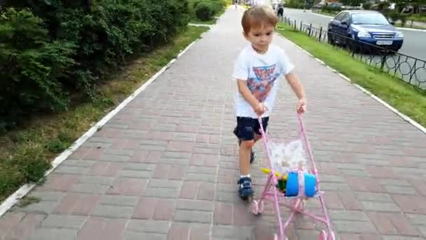 4k footage of adorable toddler boy walking on street with toy stroller for doll. Boy playing with toys for girls. Active baby