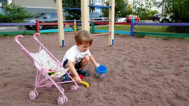 4k felvételeit aranyos kisgyermek fiú játszik a homokozóban a játszótéren a parkban