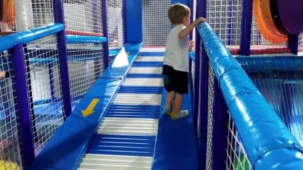 4k Video von kleinen Kleinkind Junge klettern und spielen auf weichen Spielplatz im Vergnügungspark. Aktive Kinder mit Spaß