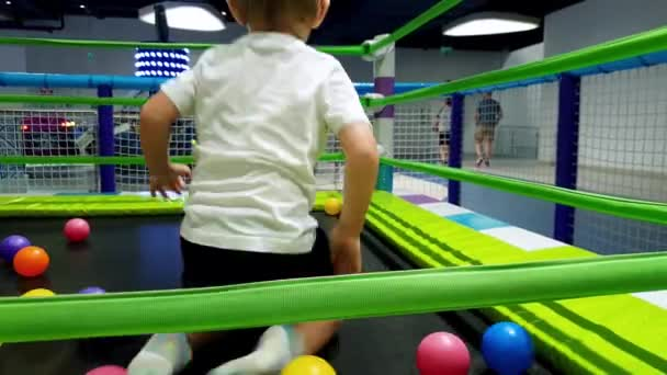4k footage of cheerful todler boy jumping pand playing on trampoline at playground. Children having fun at amusement park in shopping mall
