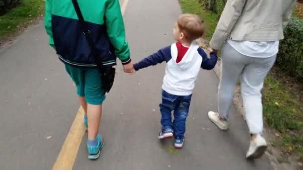 4k-Video von entzückend lächelndem Kleinkind, das seine Mutter und seinen älteren Bruder bei einem Spaziergang im Park an der Hand hält