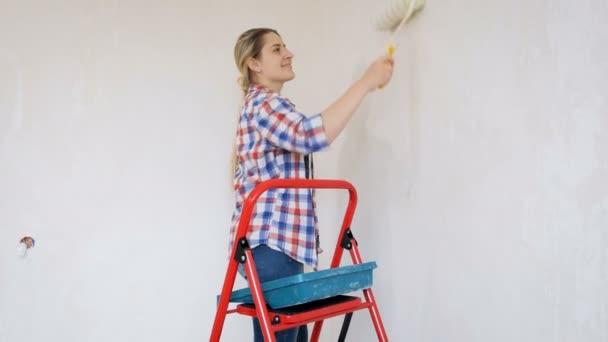 Video der schönen jungen Frau im karierten Hemd bei Renovierungsarbeiten in ihrem Haus. junges Mädchen bemalt Wände mit Farbroller