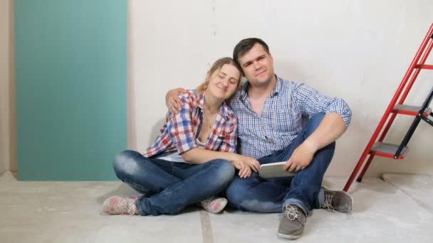 4k Filmmaterial von glücklichen jungen Paaren, die auf dem Boden ihres neuen Hauses sitzen und entspannen, das gerade renoviert wird