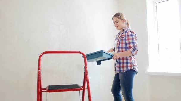 schöne junge Frau bei der Renovierung ihrer neuen Wohnung. junges Mädchen bemalt Wände in ihrem Zimmer
