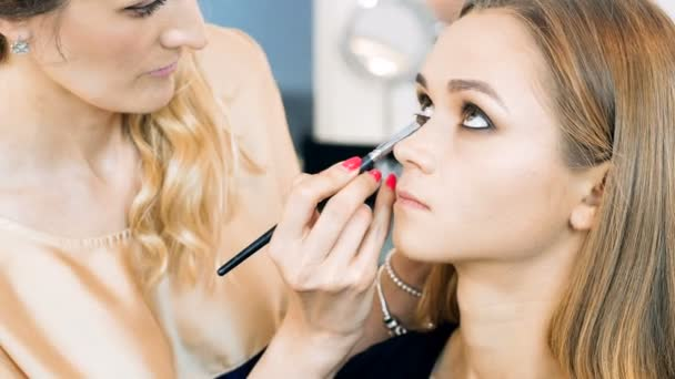 4k closeup video of professional makeup artist applying mascara and painting models eyes and brows in professional studio