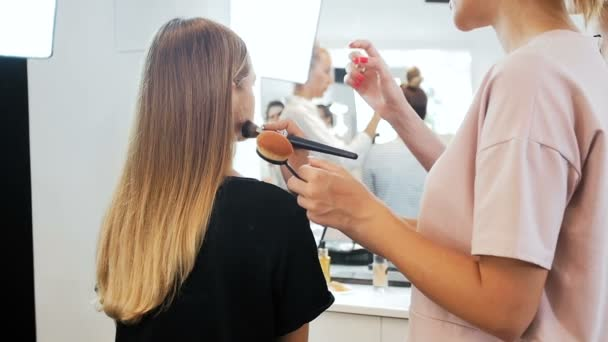 Closeup slow motion video of professional makeup artist working with model in visage studio. Woman applying cosmetics with brush