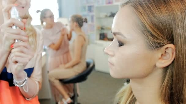 Closeup slow motion footage of professional makeup artist applying makeup on models face before fashion show