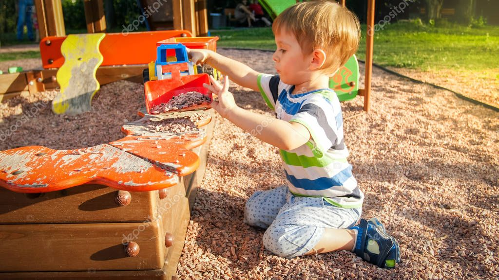 Portrait of smiling little boy sitting in the sandpit at playground and digging sand with plastic spade and pouring it in colorful toy truck with trailer