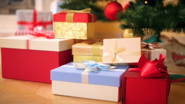 4k video of camera slowly zoming on big heap of Christmas gifts and presents lying on floor under Christmas tree. Perfect shot for your winter holidays and celebrations