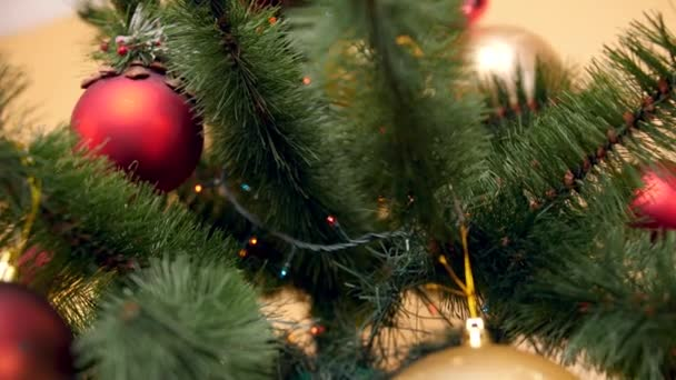 Closeup 4k panning video of camera slowly moving down the decorated Christmas tree with baubles, lights and garlands. Perfect shot for your winter holidays and celebrations