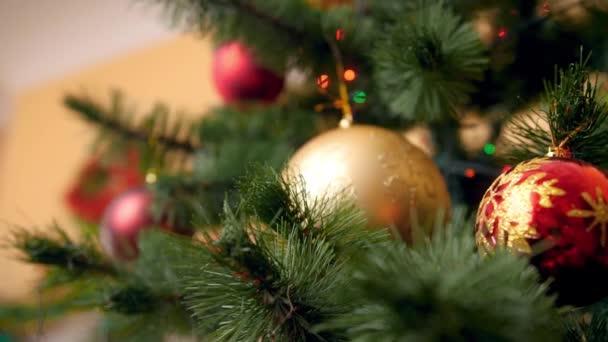 4 k odhalující záběry kamery zvolna se pohybující přes zářící barevná světla a bubny na vánočním stromku v domě