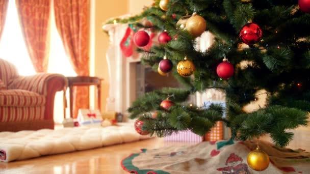 Krásné 4k záběry barevných jiskřících a zářící světel na vánočním stromku v obývacím pokoji, kde je ráno krb. Perfektní záběr na zimní prázdniny a oslavy