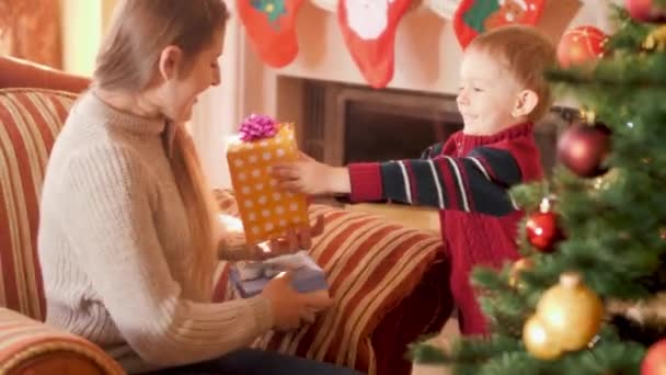 4k Video von glücklich lächelnden kleinen Jungen geben Weihnachtsgeschenk-Box mit Band zu seiner Mutter neben Weihnachtsbaum. Kind erhält Geschenke und Geschenke vom Weihnachtsmann in den Winterferien und