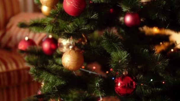 4k videó kamera lassan mozog, és pásztázza a színes izzó fények és baubles a karácsonyfa a nappaliban