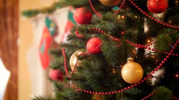 Panning 4k video o krásném vánočním stromku se spoustou bubnků, girlandů a světel. Perfektní záběr na zimní oslavy a svátky