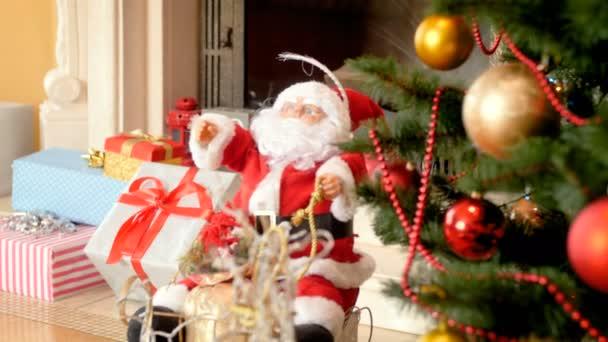 Closeup 4k video kamery zaměřené na postavu Santa Clause a pohyb na zdobený vánoční stromek. Perfektní záběr na zimní oslavy a svátky