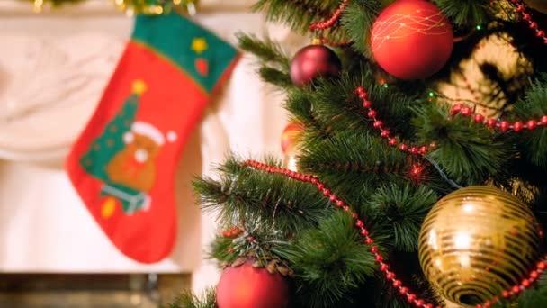 4k panning video zdobeného krbu s zavěšenými ponožkami na dárky a vánoční stromeček se spoustou barevných věnců, korálků a ozdoby. Perfektní záběr pro zimní oslavy a svátky