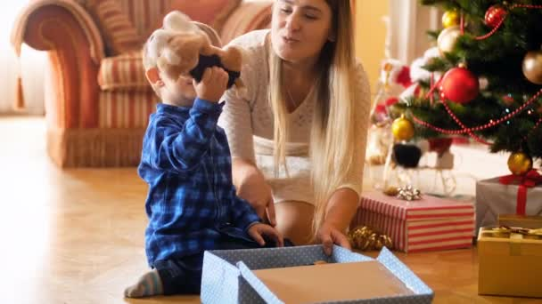 4k footage of adorable little boy opens his present box from Santa Claus and taking out toy plush dog. Family giving and receiving presents on winter holidays and celebrations.