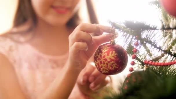 Closeup 4k videó fiatal nő üzembe piros csecsebecse a karácsonyfa ág. Családi előkészítése és mázolás ház téli ünnepek és ünnepségek.