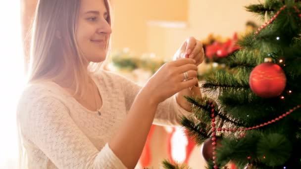 4k videó gyönyörű mosolygó nő, hosszú hajú lógott baubles és koszorúkat a karácsonyfát a nappaliban. Családi előkészítése és mázolás ház téli ünnepek és ünnepségek.
