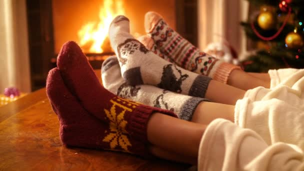 Closeup 4k footage of people in wool socks holding feet next to burning fire in fireplace at night. People relaxing on winter holidays and celebrations at home
