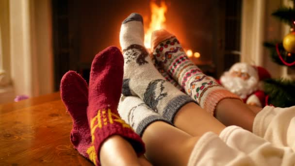 4k video of parents with child wearing warm woolen socks lying under blanket and warming at burning fireplace in living room. People relaxing on winter holidays and celebrations at home