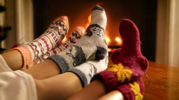 Closeup 4k footage of family wearing woolen socks holding feet next to fire in fireplace. People relaxing on winter holidays and celebrations at home