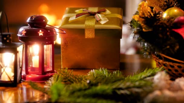 Closeup 4k footage of Christmas wreath, candle lantern and New Year present from Santa on wooden table against burning fireplace. Perfect shot for winter celebrations and holidays