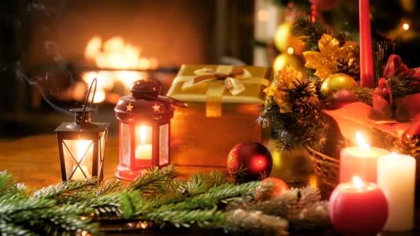 Closeup 4k panning video di candele ardenti, lanterne, regali, preents, corona di Natale e palline colorate sul tavolo contro camino ardente e albero di Natale. Colpo perfetto per le celebrazioni invernali