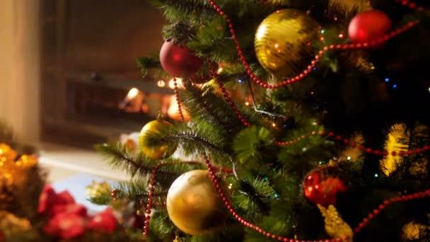 Closeup 4k záběry zářící a blikajícím barevným světlem na vánočním stromku proti spálení krbu v noci. Perfektní záběr na zimní oslavy a svátky