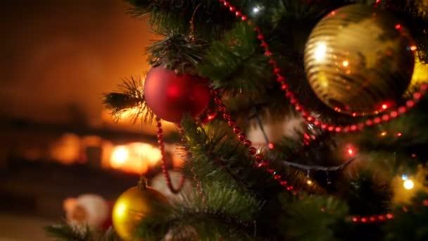 Closeup 4k záběry lesklých a třpytivých barevných světel na LED, které pokrývají vánoční stromek před krbem. Perfektní záběr na zimní oslavy a svátky
