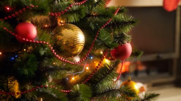 Closeup 4k záběry vánoční stromeček zdobený bazálky, girlandami a světly na oslavu nového roku proti spálení krbu v obývacím pokoji. Perfektní záběr na zimní oslavy a svátky