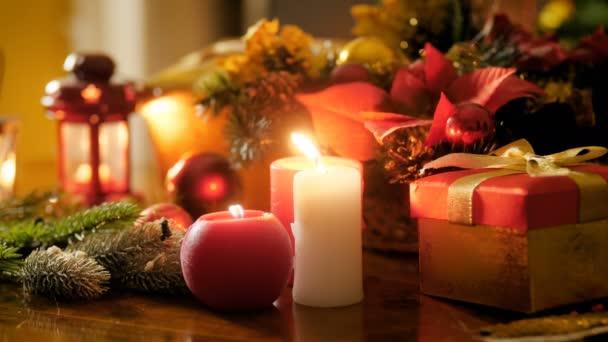 Closeup 4k záběry hořících svíček a luceren na stole vyzdobené vánočním věkem a dárky od Santa Clause. Perfektní záběr na zimní oslavy a svátky