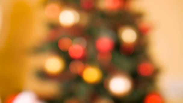 Rozostřené video barevných zářících vánočních světel na vánočním stromku. Perfektní záběr na zimní oslavy a svátky