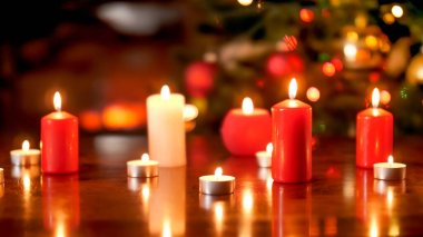Beautiful Christmas background with burning white and red candles on wooden table