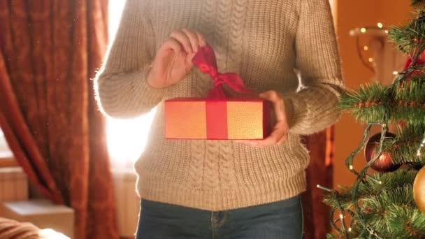 4k felvétel fiatal nőről, amint kioldja a piros szalagot és kinyitja a dobozt karácsonyi ajándékkal reggel
