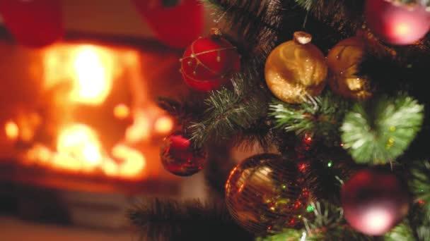 Szekrény tónusú videó karácsonyfa ágak baubles és fények ellen égő kandalló