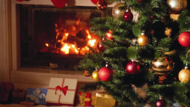 4k video of big heap of gifts and present next to burning fireplace and glowing Christmas tree in living room on Christmas eve