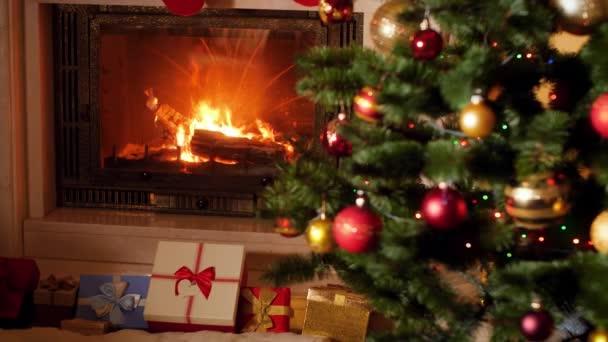 4k Filmmaterial von vielen Weihnachtsgeschenken und Geschenken unter dem Weihnachtsbaum neben dem brennenden Kamin im Wohnzimmer
