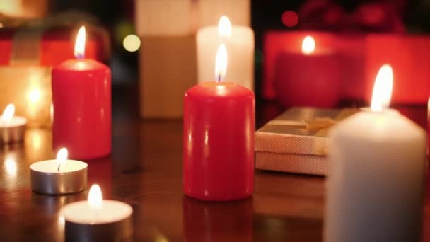Dolly 4k video of lots of advent candles and boxes with Christmas gifts and present on wooden table. Perfect background or backdrop for Christmas or New Year